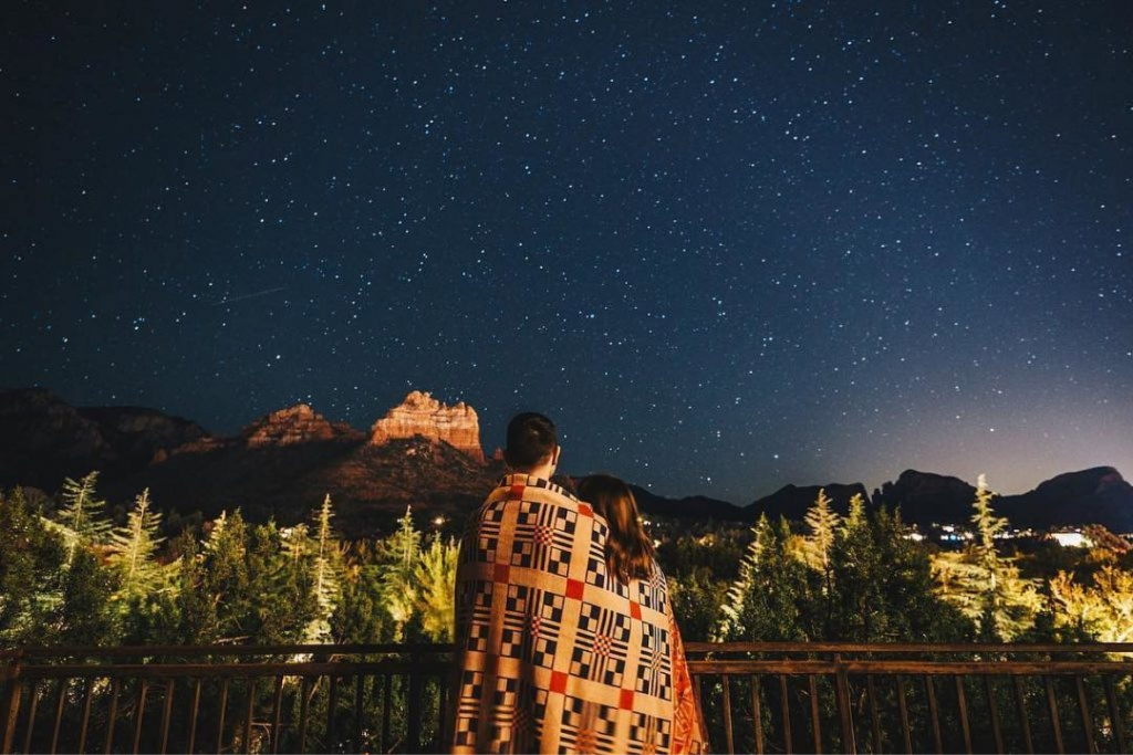 A couple wrapped in a blanket gazing at the star filled night sky.