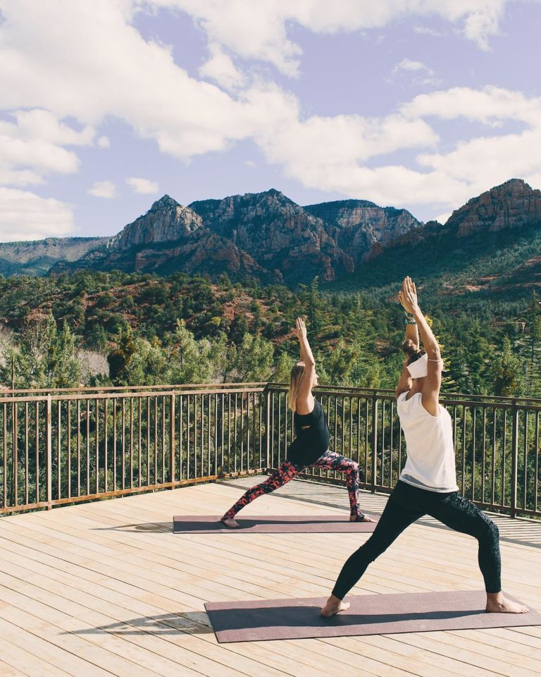 Two women practicing yoga on a sunny deck