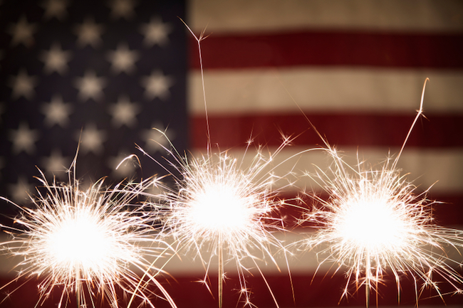 3 sparklers ignited with the American flag as background
