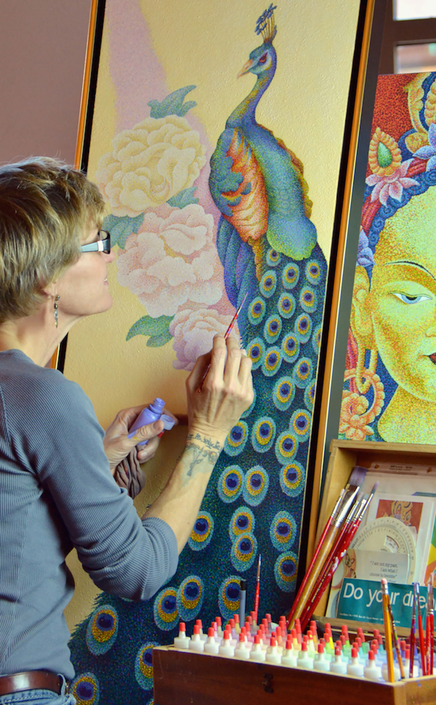 Artist Sherab Khandro painting a peacock