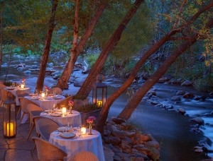 Restaurant tables set alongside a stream at dusk