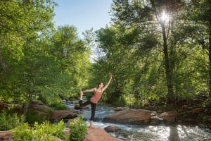 A woman practicing yoga beside a tree lined stream
