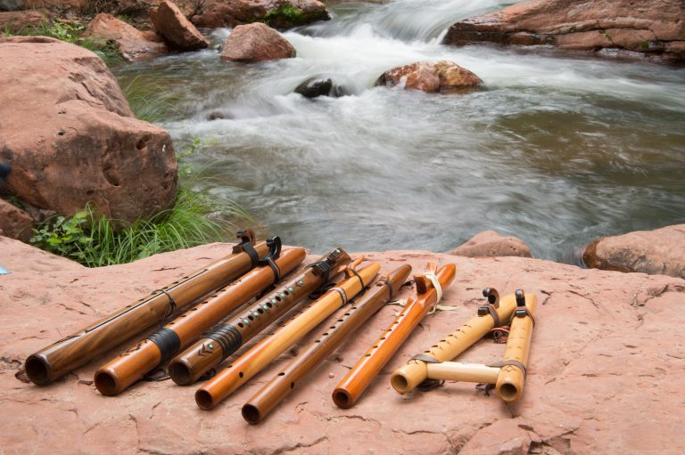 Wooden flutes lying on a rock beside a creek