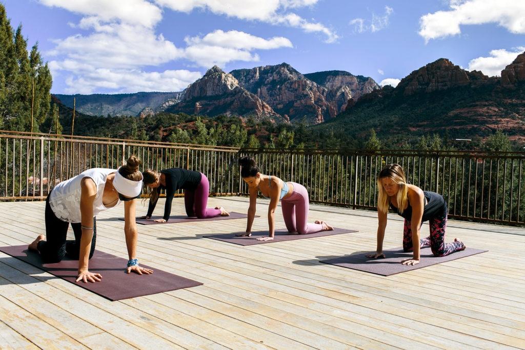 Women doing yoga position table, outside overlooking mountains.