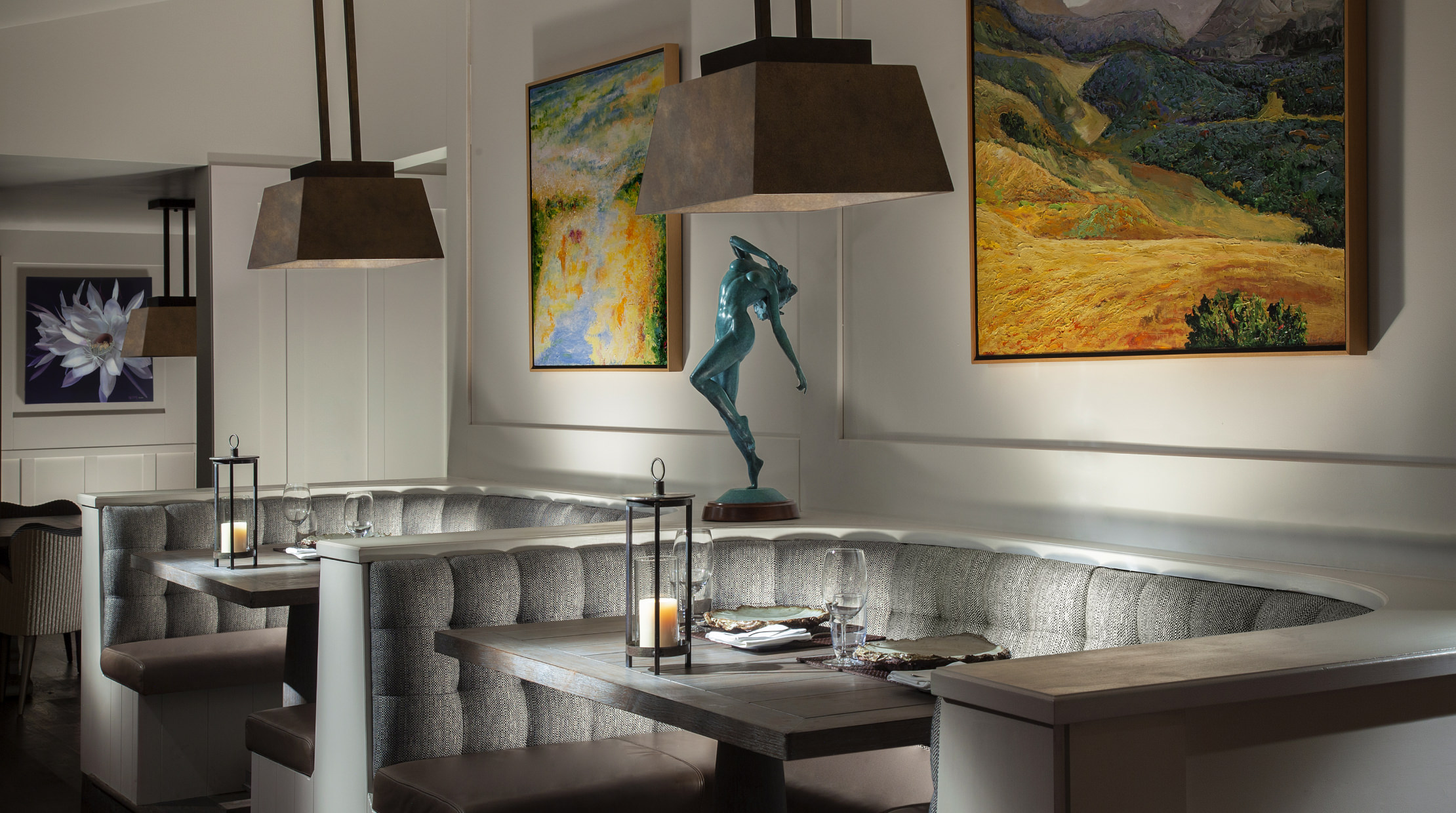 Half circle dining booths with art on the walls