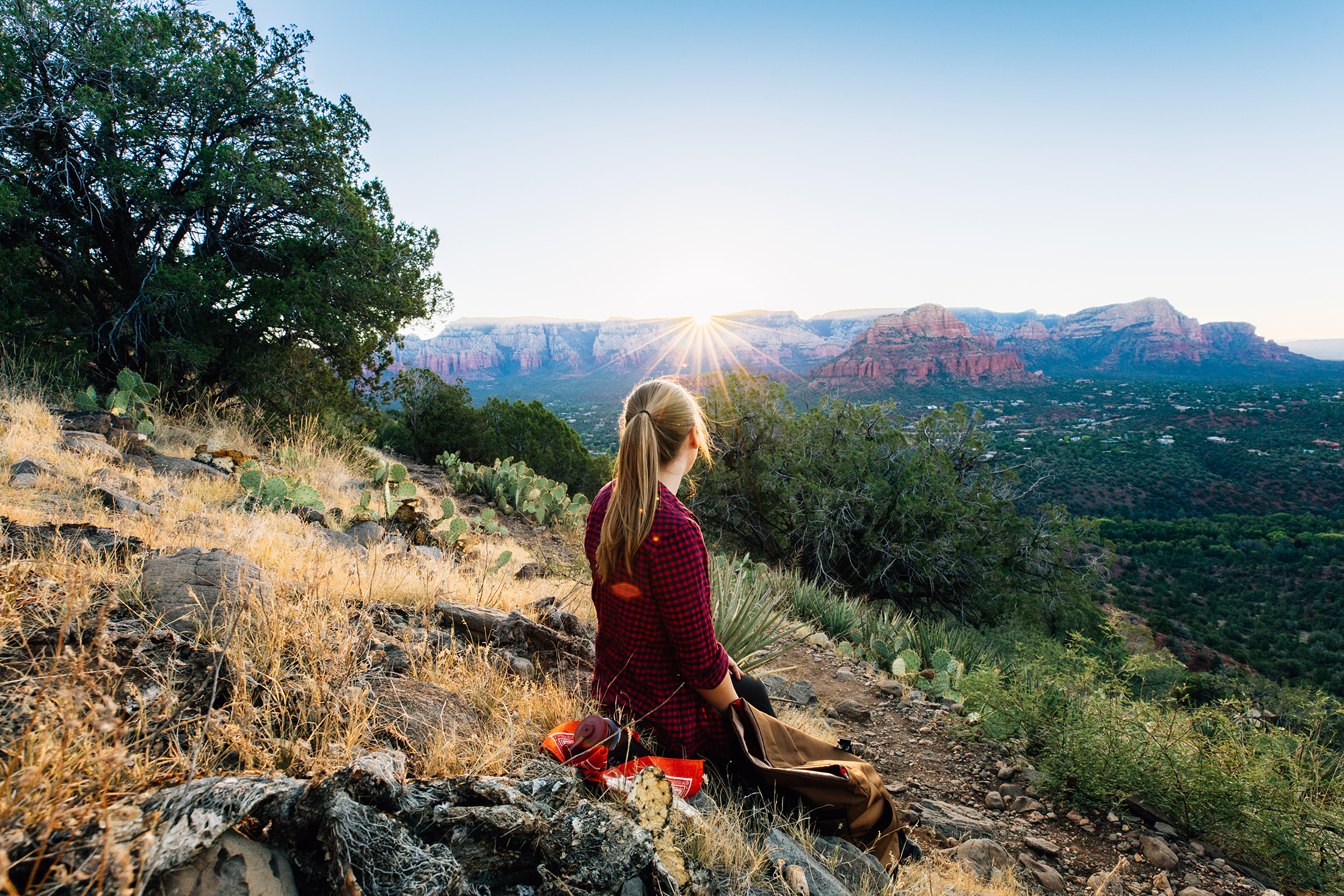 Woman sits on a hilltop overlooking the mesa as the sun rises on the horizon.