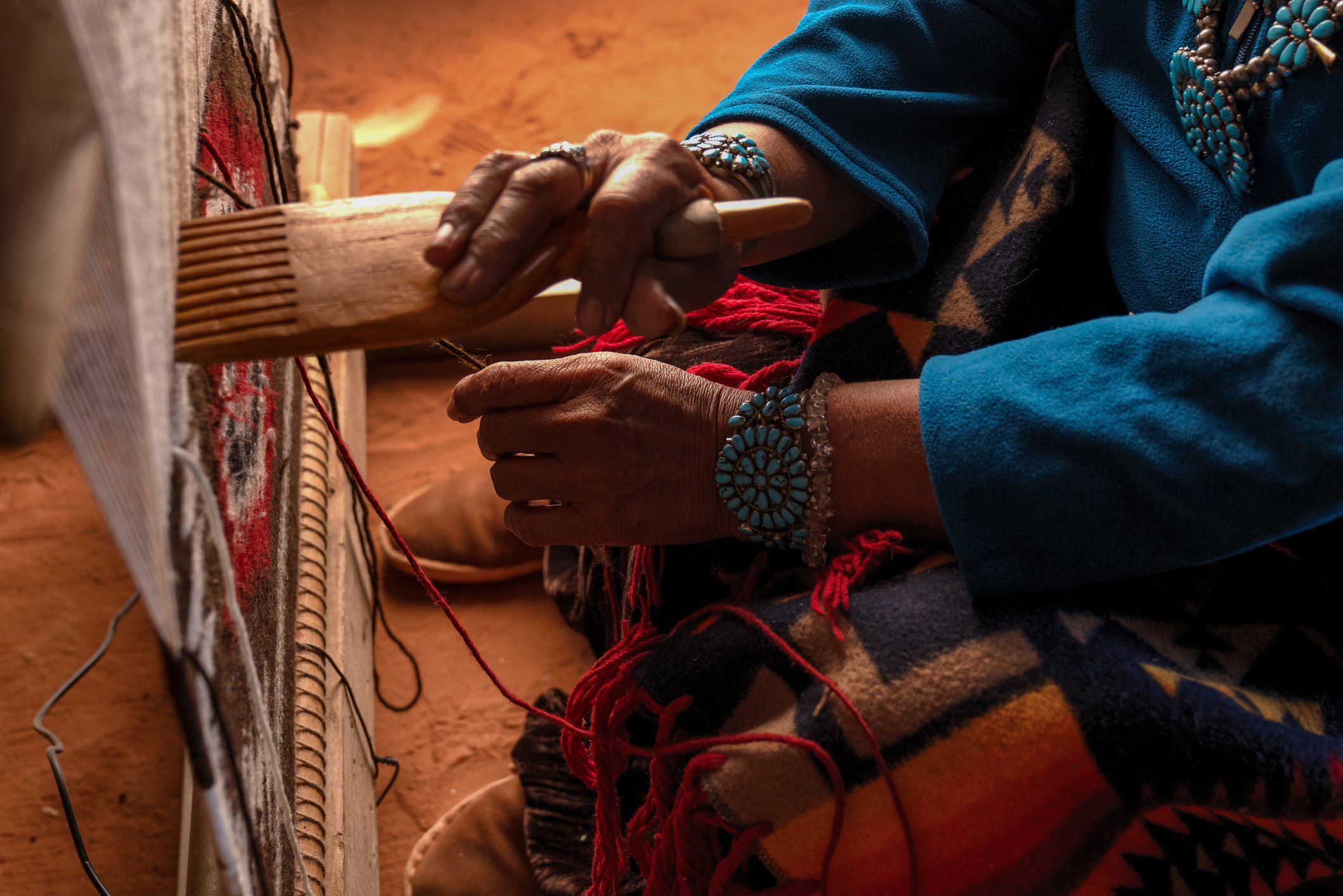 Traditional Navajo elderly woman working on a blanket loom in an authentic hogan