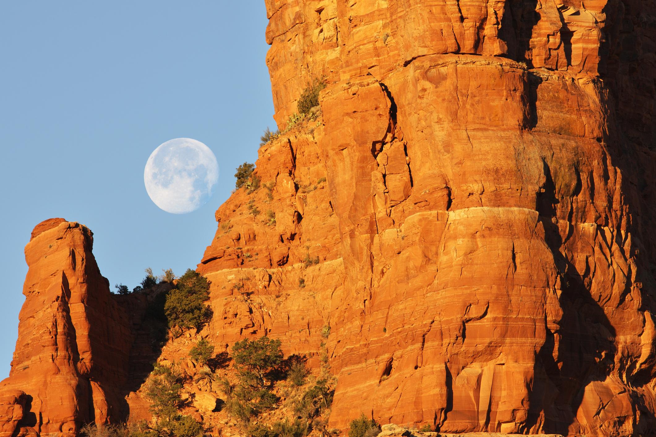Full moon descends behind red rock desert butte as morning sun rises.