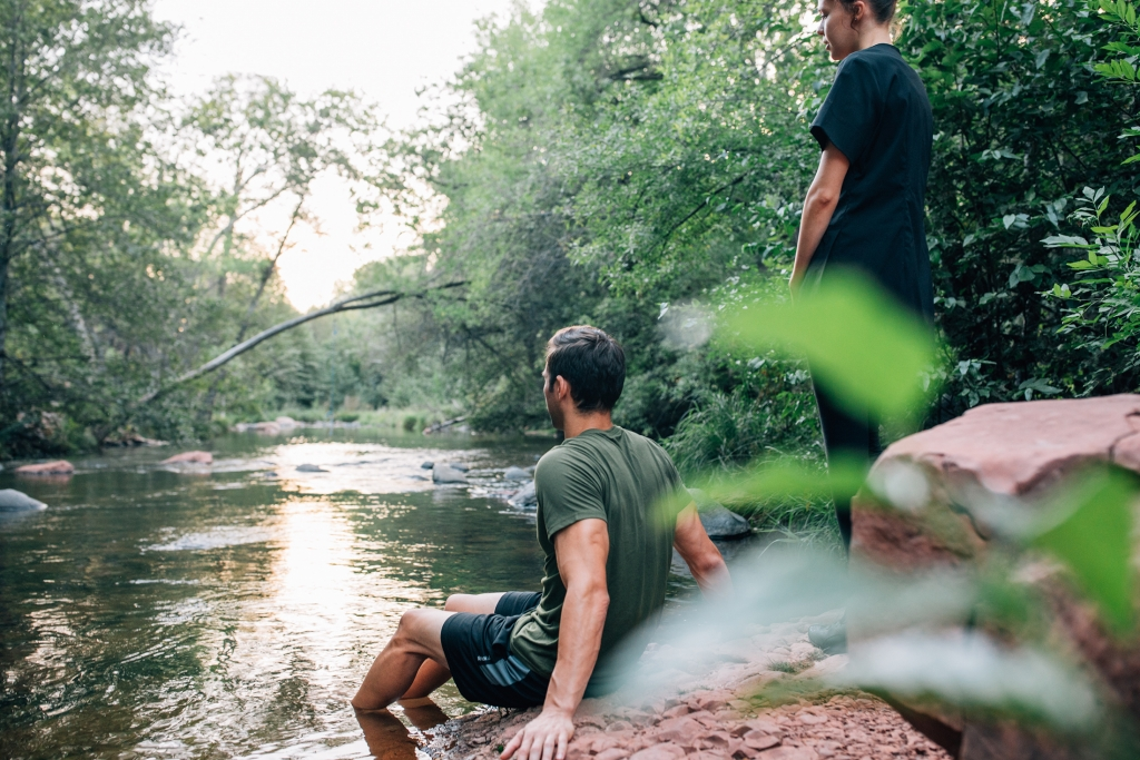A man in tshirt and shorts sits at the edge of a stream with feel in water
