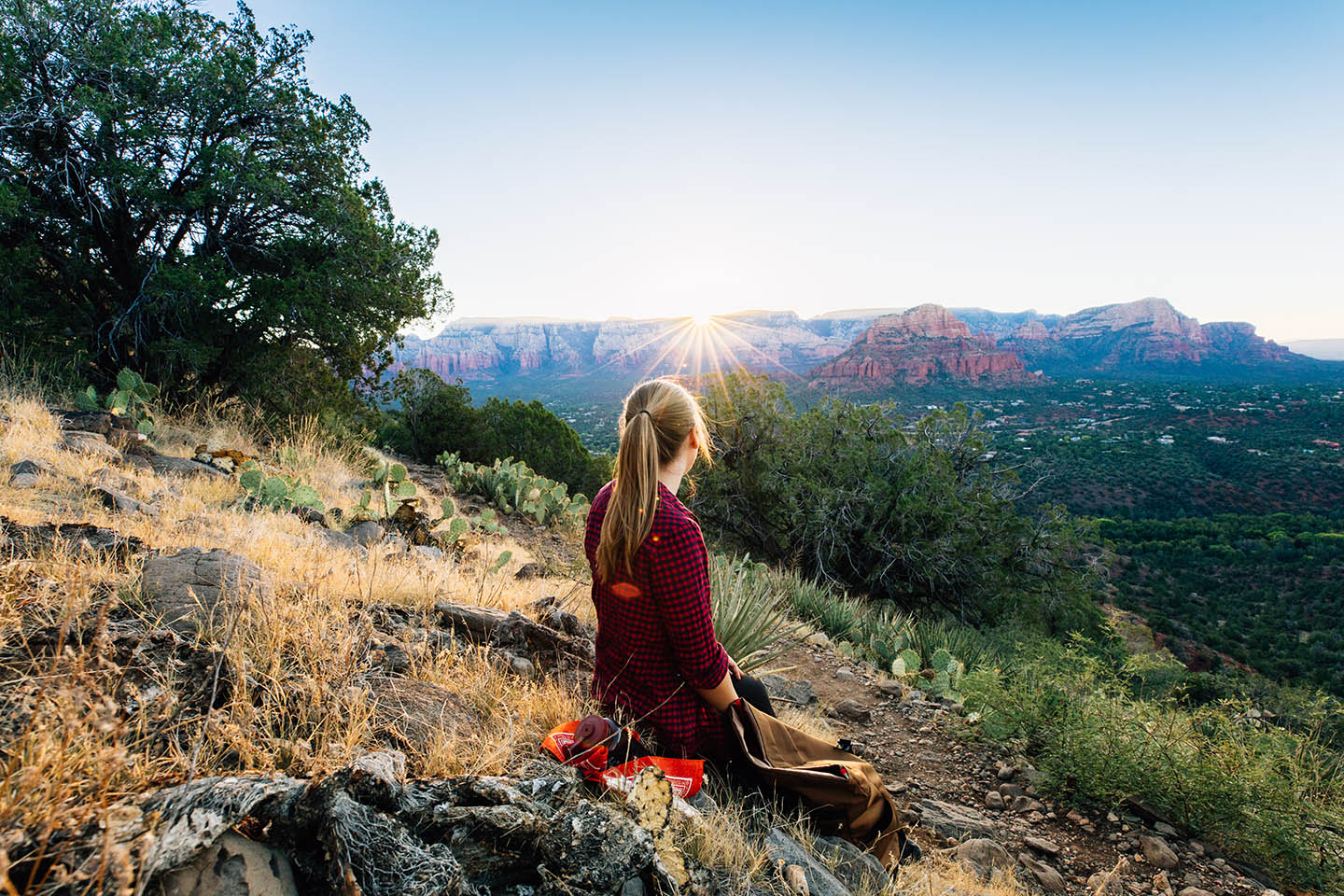 a woman sits on a hilltop looking away at the sun rising over the mesa