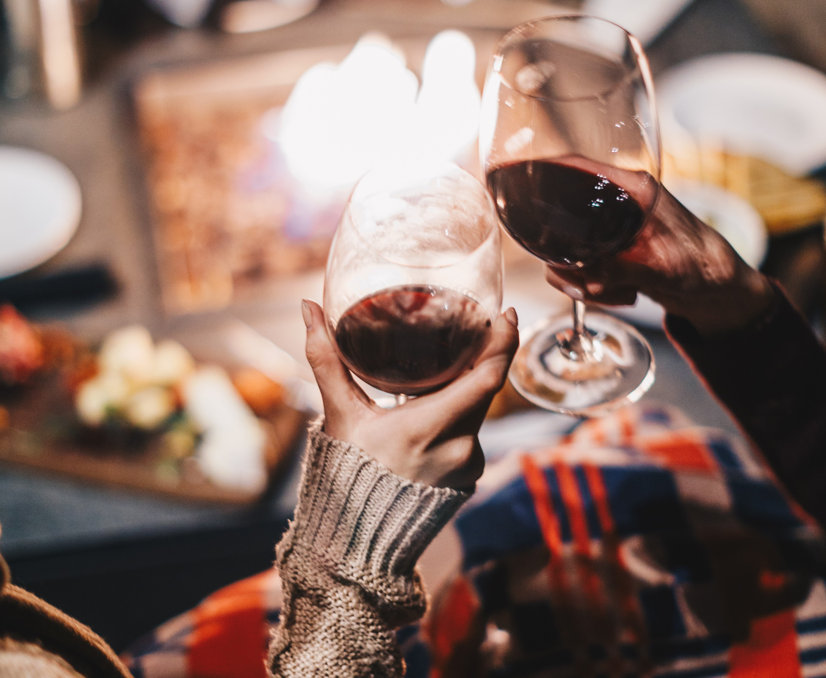 Close up of two hands clinking wine glasses over a cheese board and fire pit