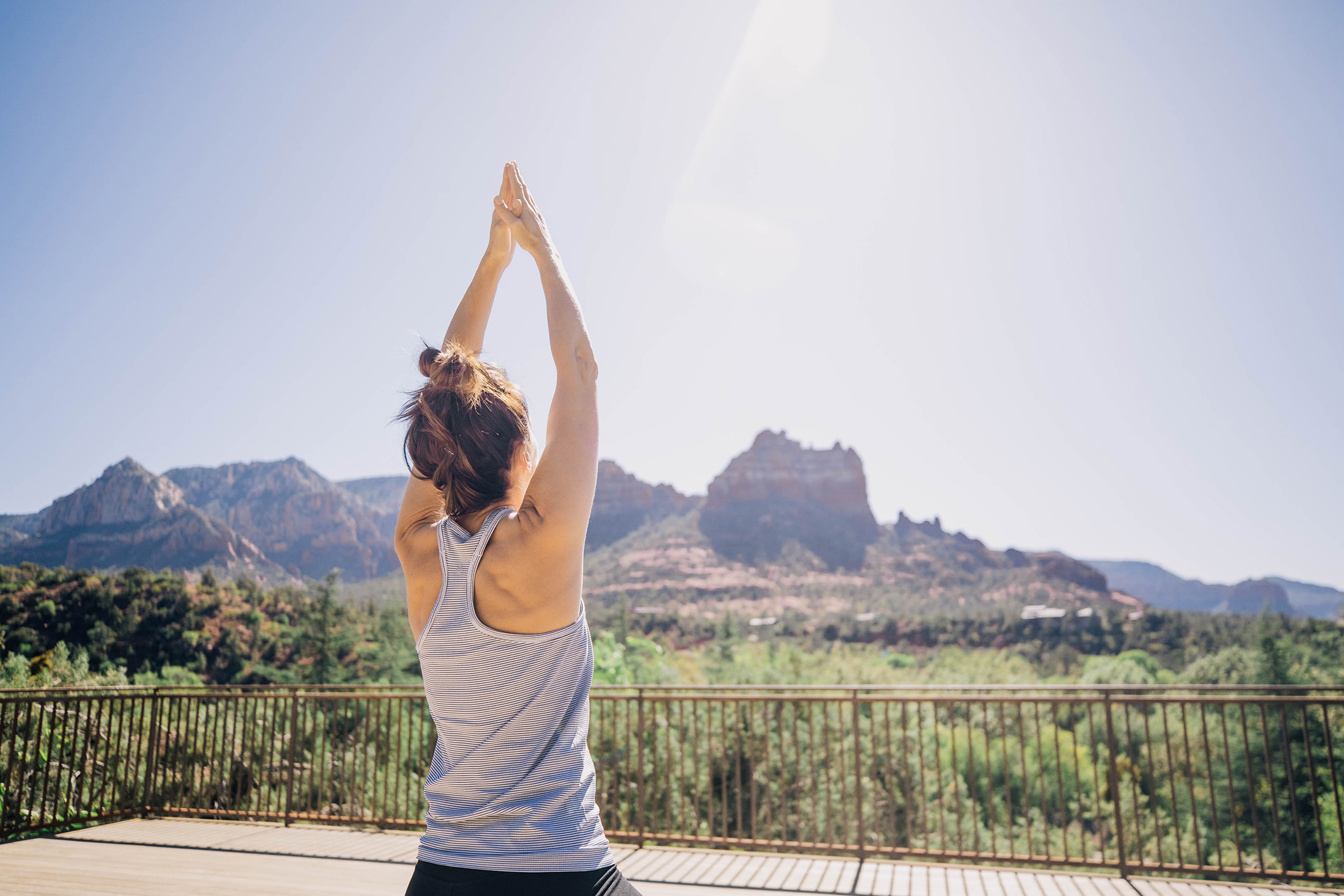 A woman practicing yoga outside looking out at the tall mesas in the distance